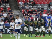 Portland Timbers players celebrate after a Vancouver Whitecaps own goal during the second half of an MLS soccer match Friday, Sept. 10, 2021, in Vancouver, British Columbia.