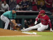 Los Angeles Angels designated hitter Shohei Ohtani, right, slides into third for a an RBI triple ahead of the tag of Seattle Mariners third baseman Kyle Seager during the third inning of a baseball game Saturday, Sept. 25, 2021, in Anaheim, Calif. (AP Photo/Mark J.