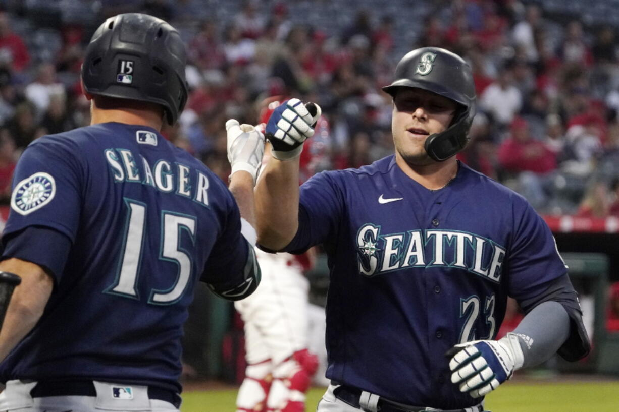 Seattle Mariners' Ty France is congratulated by Kyle Seager after hitting a solo home run during the first inning of a baseball game against the Los Angeles Angels Friday, Sept. 24, 2021, in Anaheim, Calif. (AP Photo/Mark J.
