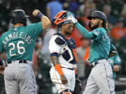 Seattle Mariners' J.P. Crawford (3) celebrates with Jose Marmolejos (26) after both scored on Crawford's two-run home run as Houston Astros catcher Martin Maldonado looks down during the ninth inning of a baseball game Wednesday, Sept. 8, 2021, in Houston. (AP Photo/David J.