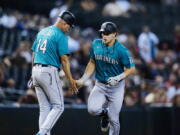 Seattle Mariners' Jarred Kelenic, right, celebrates his two-run home run against the Arizona Diamondbacks with Mariners third base coach Manny Acta (14) during the sixth inning of a baseball game Friday, Sept. 3, 2021, in Phoenix. (AP Photo/Ross D.