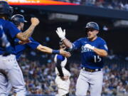 Seattle Mariners' Kyle Seager (15) celebrates his three-run home run against the Arizona Diamondbacks with Mariners' J.P. Crawford, left, and Mitch Haniger during the first inning of a baseball game Saturday, Sept. 4, 2021, in Phoenix. (AP Photo/Ross D.