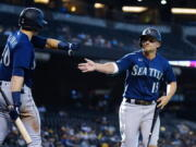 Seattle Mariners' Kyle Seager (15) celebrates his run scored against the Arizona Diamondbacks with teammate Jarred Kelenic (10) during the 11th inning of a baseball game Sunday, Sept. 5, 2021, in Phoenix. (AP Photo/Ross D.