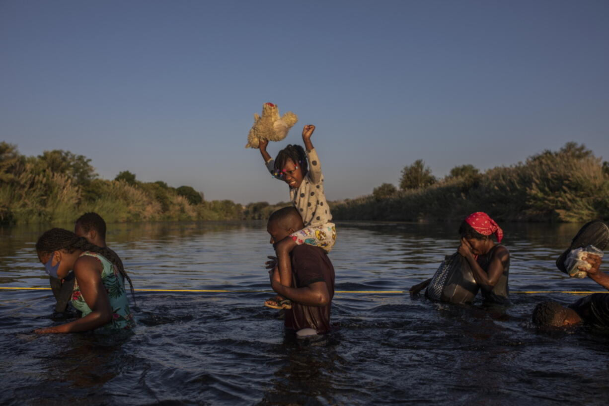 Migrants wade across the Rio Grande from Del Rio, Texas, to Ciudad Acu?a, Mexico, to shop for food and supplies before returning back to the US side of the border, Sunday, Sept. 19, 2021. Thousands of Haitian migrants have been arriving to Del Rio, Texas, as authorities attempt to close the border to stop the flow of migrants.