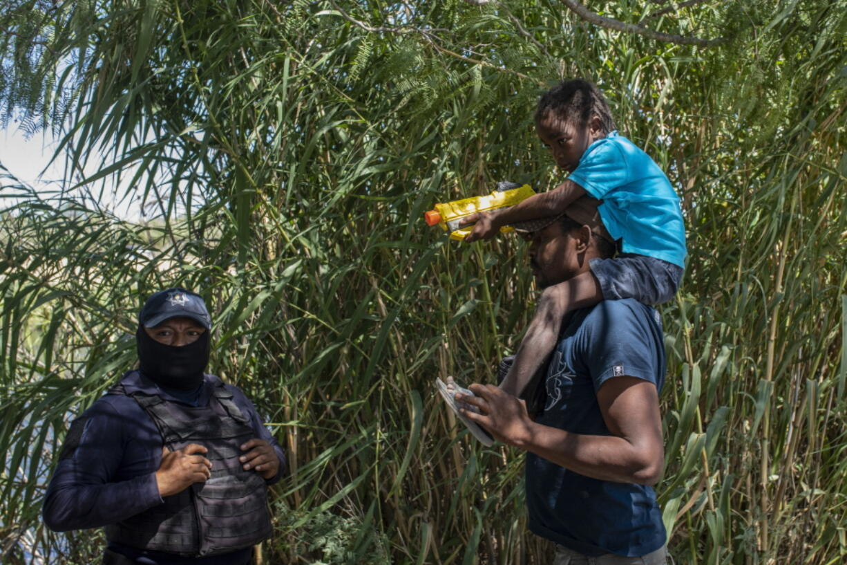 A Haitian migrant talks to with a Mexican police officer blocking access to the Rio Grande river so that immigrants can't use it to cross the U.S.-Mexico border from Ciudad Acuna, Mexico, Thursday, Sept. 23, 2021.