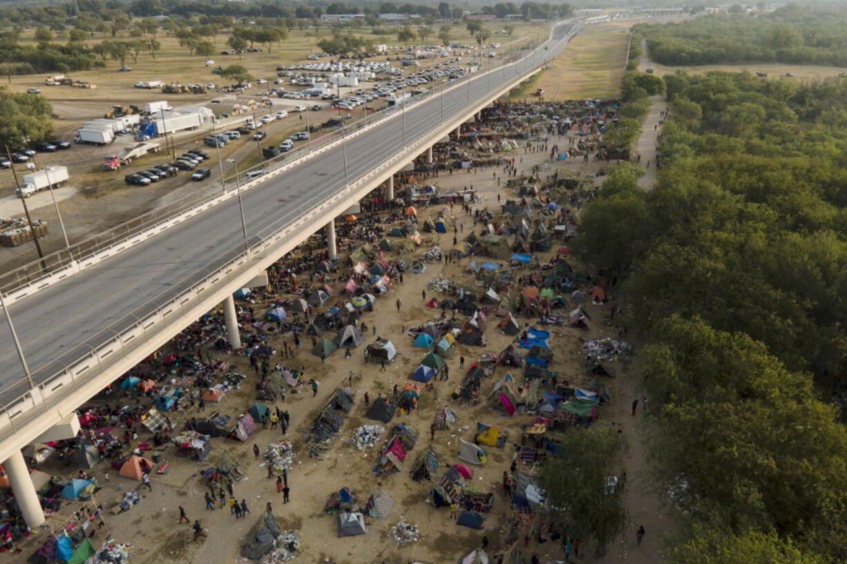 Migrants, many from Haiti, are seen at an encampment along the Del Rio International Bridge near the Rio Grande, Tuesday, Sept. 21, 2021, in Del Rio, Texas.  The options remaining for thousands of Haitian migrants straddling the Mexico-Texas border are narrowing as the United States government ramps up to an expected six expulsion flights to Haiti and Mexico began busing some away from the border.