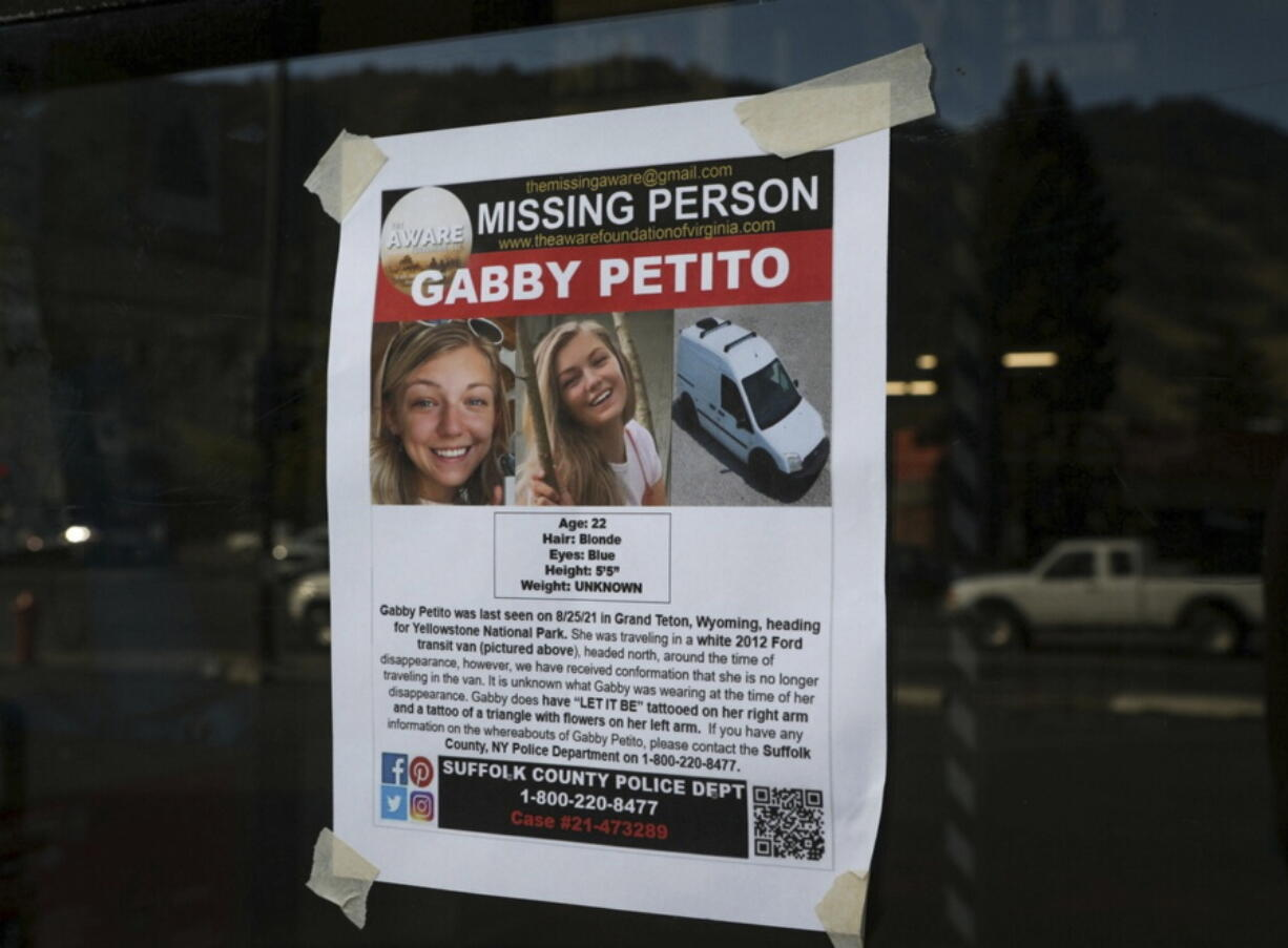 This Thursday, Sept. 16, 2021, photo, shows a Suffolk County Police Department missing person poster for Gabby Petito posted in Jakson, Wyo. Petito, 22, vanished while on a cross-country trip in a converted camper van with her boyfriend. Authorities say a body discovered Sunday, Sept. 19 in Wyoming, is believed to be Petito.