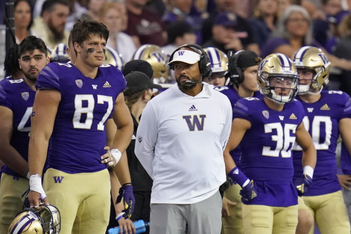 Washington head coach Jimmy Lake, center, stands on the sidelines late in the second half of Saturday's loss to 13-7 Montana in Seattle.