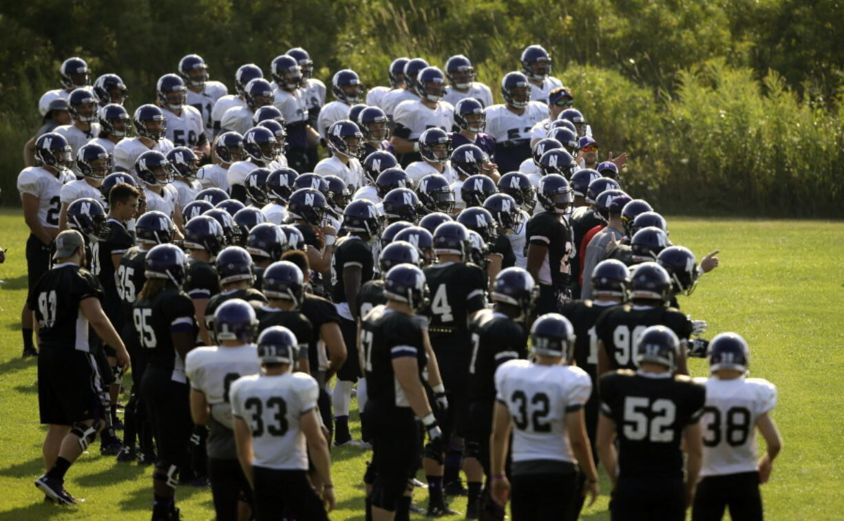 FILE - Northwestern football players gather during practice at the University of Wisconsin-Parkside campus in Kenosha, Wisc., in this Monday, Aug. 17, 2015, file photo. College football players and some other athletes in revenue-generating sports are employees of their schools, the National Labor Relations Board's top lawyer said in a memo Wednesday, Sept. 29, 2021, that would allow the players to unionize and otherwise negotiate over their working conditions.