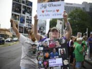"""FILE - In this Aug. 17, 2018, file photo, Lynn Wencus of Wrentham, Mass., holds a sign with a picture of her son Jeff and wears a sign of others' loved ones lost to OxyContin and other opioids during a protest at Purdue Pharma LLP headquarters in Stamford, Conn. A landmark settlement in the nation's opioid epidemic is forcing the owners of OxyContin maker Purdue Pharma to give up the company and pay out $4.5 billion. """"Am I happy they don't have to admit guilt and give up all their money? Of course not,"""" said Wencus. """"But what would that do?"""