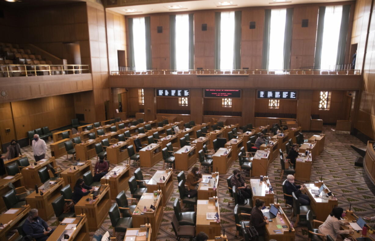 Oregon State Representatives congregate in the House, prior to the meeting being adjourned due to a COVID-19 exposure, during a special legislative session for redistricting congressional maps, Tuesday, Sept.