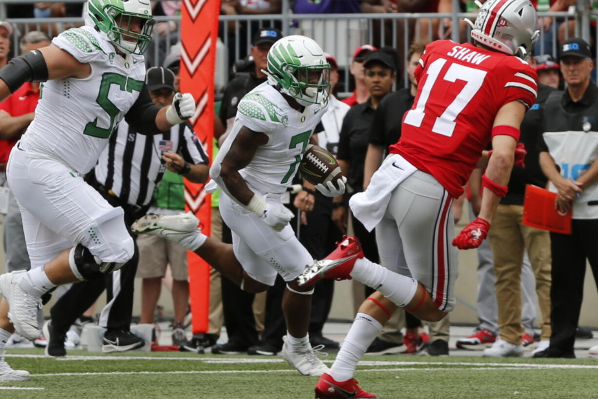 Oregon running back CJ Verdell, center, scores a touchdown against Ohio State during the first half of an NCAA college football game Saturday, Sept. 11, 2021, in Columbus, Ohio.