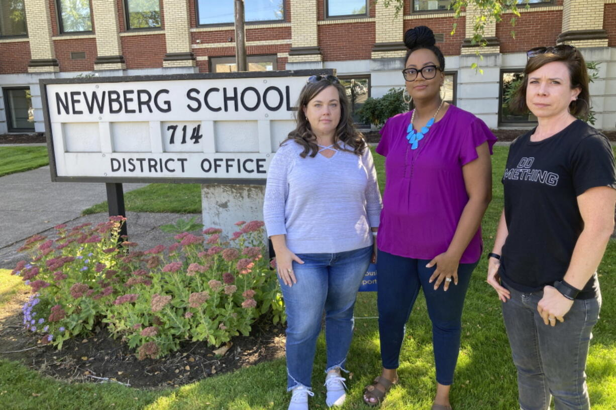 From left, Beth Woolsey, Tai Haden-Moore and AJ Schwanz , who are members of a group called Newberg Equity in Education which is advocating for inclusion and equity in schools, stand in front of a school district office in Newberg, Ore., on Tuesday, Sept. 21, 2021. The Newberg School Board has banned educators from displaying Black Lives Matter and gay pride symbols, prompting a torrent of recriminations and threats to boycott the town and its businesses.