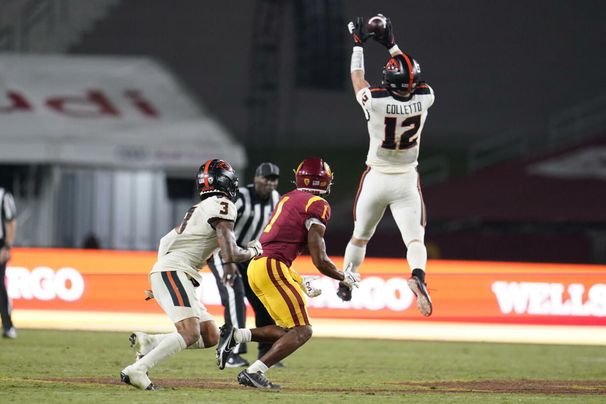 Oregon State linebacker Jack Colletto (12) jumps in front of Southern California wide receiver Gary Bryant Jr. (1) to intercept a pass during the second half of an NCAA college football game Saturday, Sept. 25, 2021, in Los Angeles.