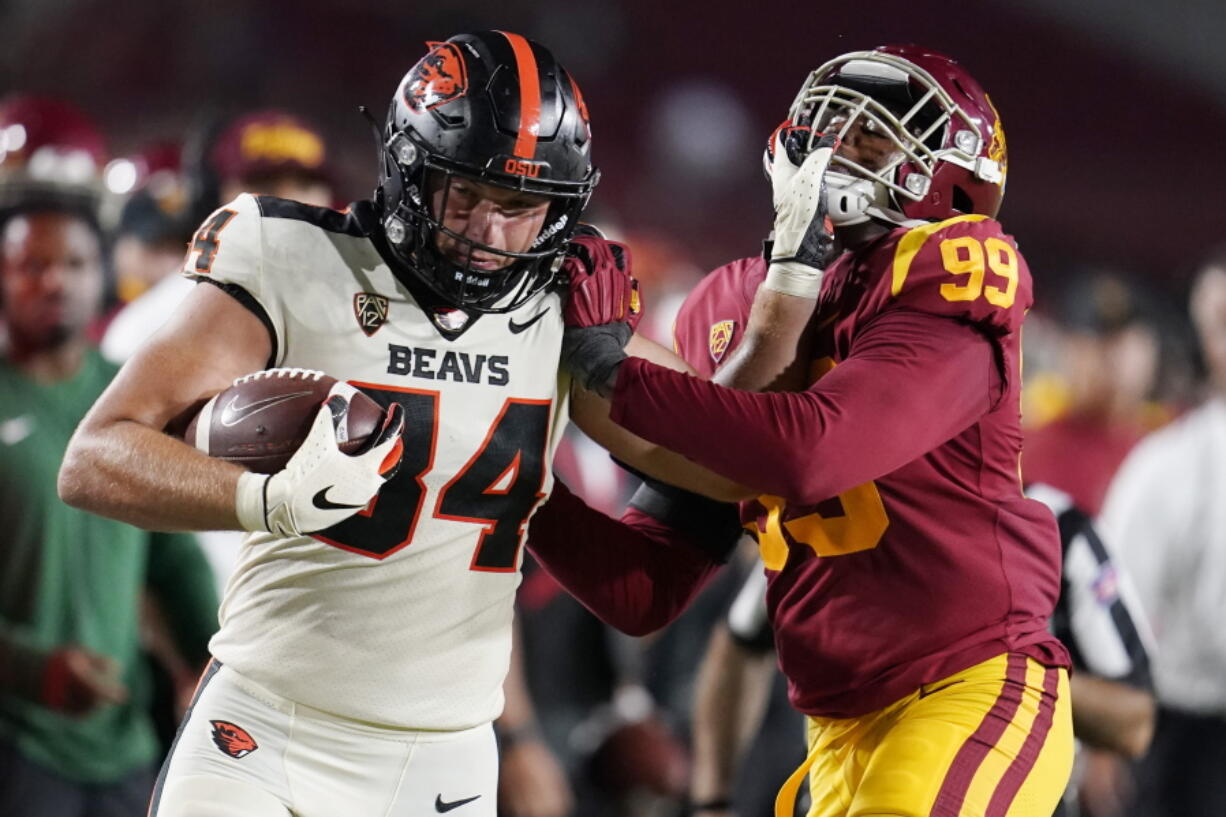 Oregon State tight end Teagan Quitoriano (84) stiff-arms Southern California linebacker Drake Jackson (99) after a reception during the second half of an NCAA college football game Saturday, Sept. 25, 2021, in Los Angeles.
