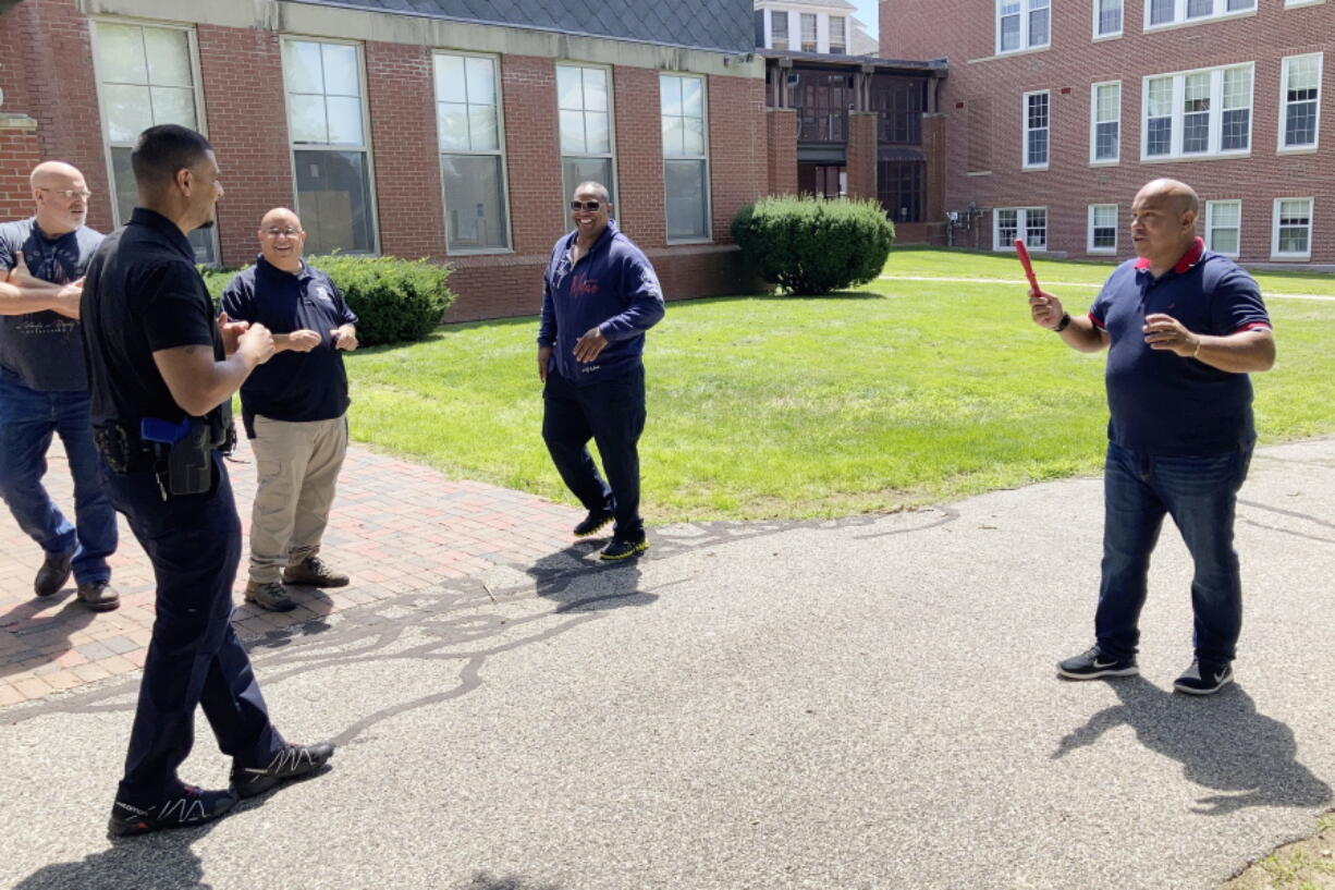 In this July 28, 2021 photo, Jose Otero from the New York City Police Department, right, holds a plastic knife after completion of a role-playing scenario in which New England police officers were learning de-escalation techniques from the Police Executive Research Forum in Saco, Maine.