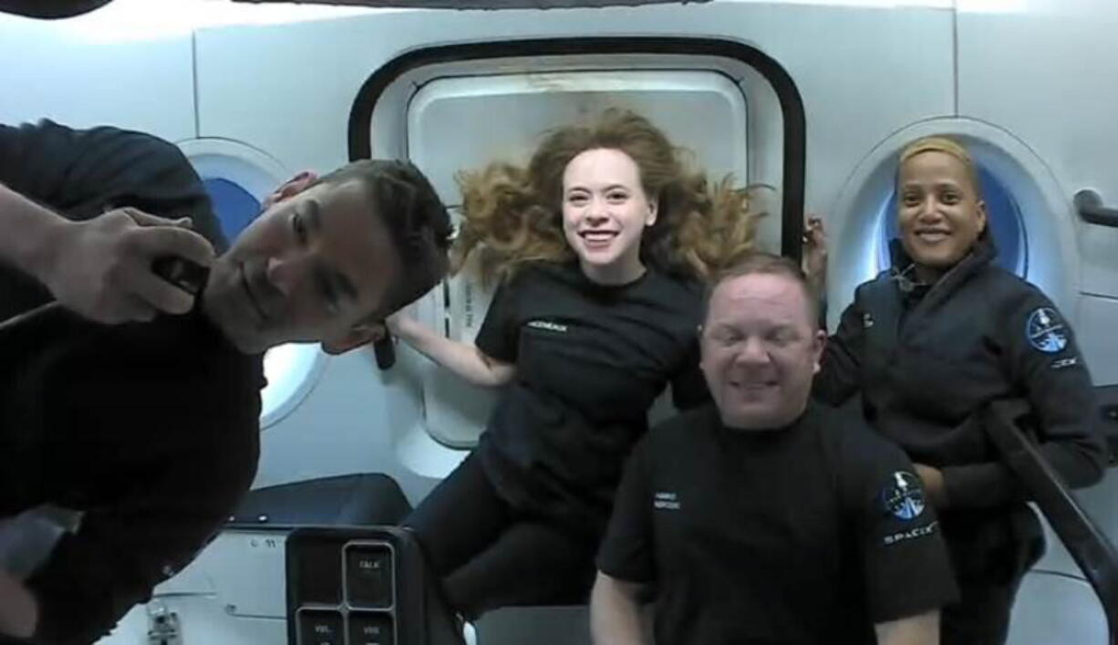 This photo provided by SpaceX shows the passengers of Inspiration4 in the Dragon capsule on their first day in space. They are, from left, Jared Isaacman, Hayley Arceneaux, Chris Sembroski and Sian Proctor.   SpaceX got them into a 363-mile (585-kilometer) orbit following Wednesday night's launch from NASA's Kennedy Space Center. That's 100 miles (160 kilometers) higher than the International Space Station.
