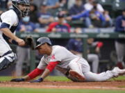 Boston Red Sox's Rafael Devers, right, scores as Seattle Mariners catcher Tom Murphy waits for the ball in the 10th inning of a baseball game Wednesday, Sept. 15, 2021, in Seattle.