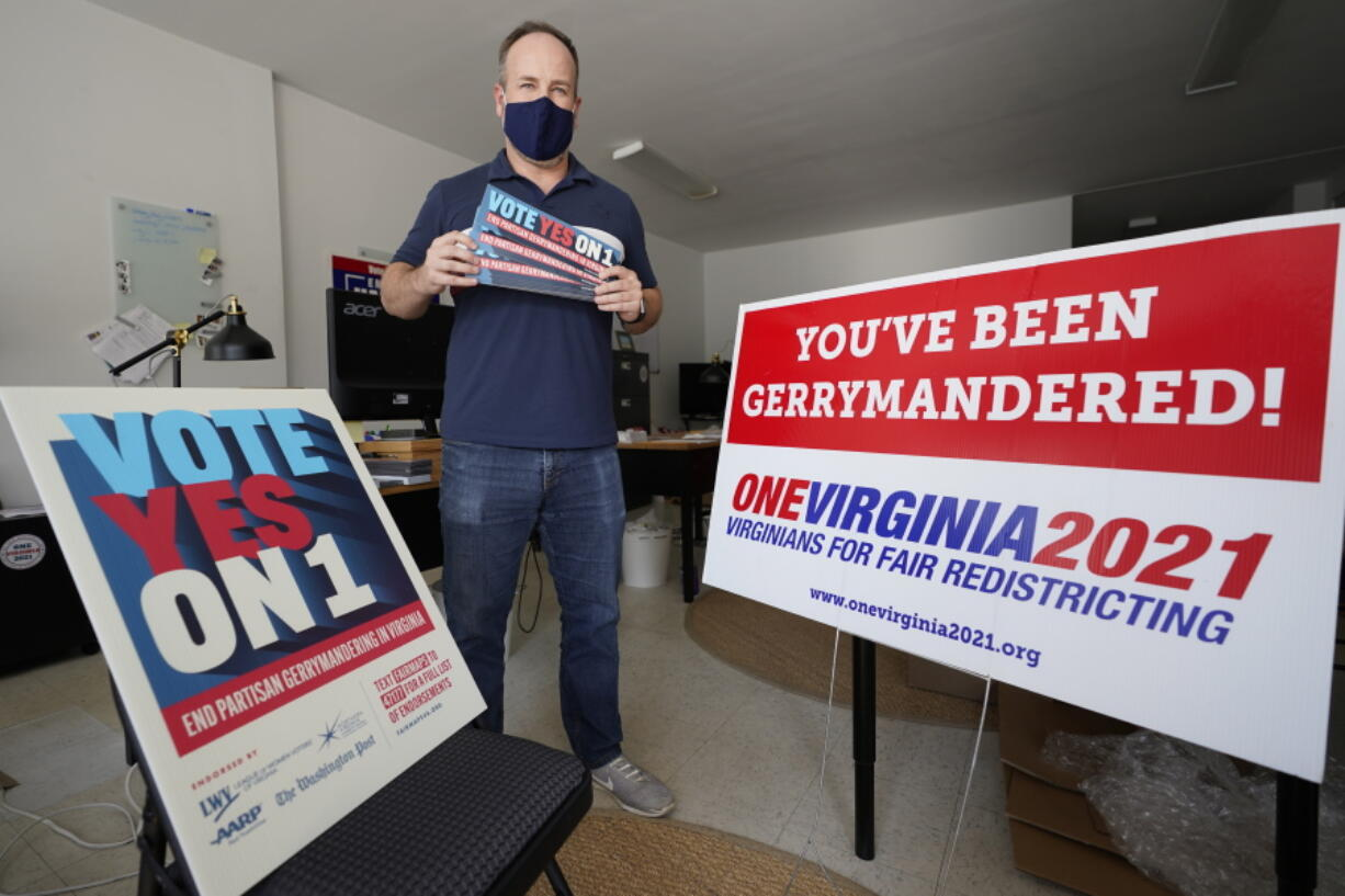 FILE - In this Oct. 6, 2020 file photo, redistricting reform advocate Brian Cannon poses with some of his yard signs and bumper stickers in his office in Richmond, Va.  A new voter-approved commission in Ohio that was supposed to reduce partisanship in the once-a-decade process of political map-drawing has already become a flop.  Similar commissions meeting for the first time in New York and Virginia have devolved into partisan finger-pointing, undermining their intent.