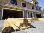 In this June 24, 2021 photo, lumber is piled at a housing construction site in Middleton, Mass.  Rising costs and shortages of building materials and labor are rippling across the homebuilding industry, which accounted for nearly 12% of all U.S. home sales in July. Construction delays are common, prompting many builders to pump the brakes on the number of new homes they put up for sale. As building a new home gets more expensive, some of those costs are passed along to buyers.