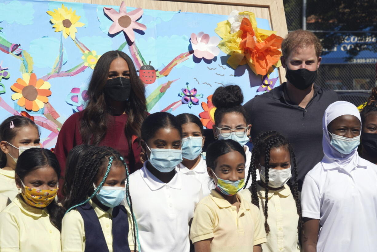 Prince Harry and Meghan, the Duke and Duchess of Sussex, pose for photos with a group of third grade students during their visit to P.S. 123, the Mahalia Jackson School, in New York's Harlem neighborhood, Friday, Sept. 24, 2021.