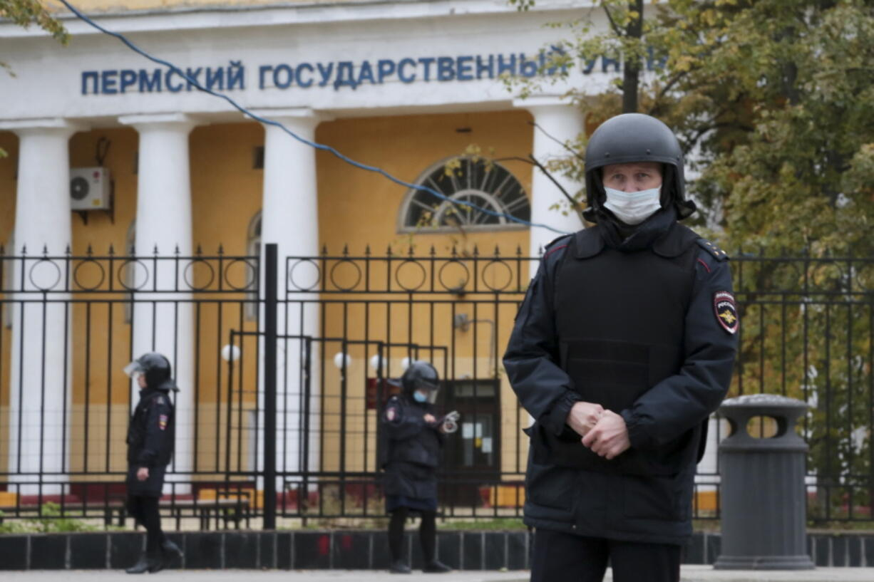 Police officers guard an area in front of the Perm State University in Perm, about 1,100 kilometers (700 miles) east of Moscow, Russia, Monday, Sept. 20, 2021. A gunman opened fire in a university in the Russian city of Perm on Monday morning, leaving at least eight people dead and others wounded, according to Russia's Investigative Committee.