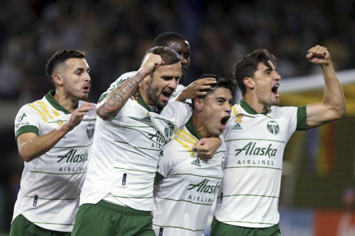 Portland Timbers forward Felipe Mora, second from right, and teammates celebrate his second-half goal against the Colorado Rapids during an MLS soccer match Wednesday, Sept. 15, 2021, in Portland, Ore.
