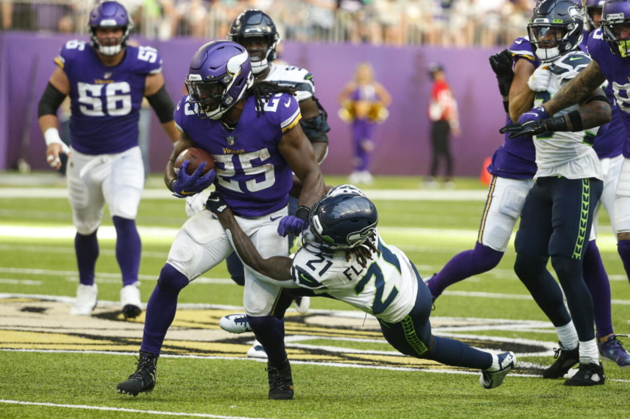 Minnesota Vikings running back Alexander Mattison (25) is tackled by Seattle Seahawks cornerback Tre Flowers (21) in the first half of an NFL football game in Minneapolis, Sunday, Sept. 26, 2021.