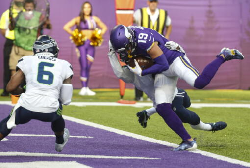 Minnesota Vikings wide receiver Adam Thielen (19) scores a touchdown on a catch in front of Seattle Seahawks strong safety Quandre Diggs (6) in the first half of an NFL football game in Minneapolis, Sunday, Sept. 26, 2021.