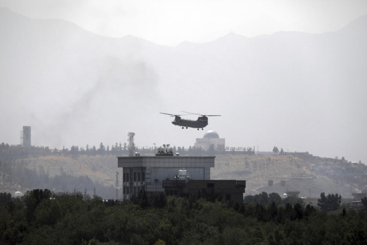 ADVANCE FOR PUBLICATION ON FRIDAY, SEPT. 10, AND THEREAFTER - FILE - In this Sunday, Aug. 15, 2021 file photo, a U.S. Chinook helicopter flies over the U.S. embassy in Kabul, Afghanistan. Helicopters landed at the embassy as diplomatic vehicles left the compound amid the Taliban advance on the Afghan capital.