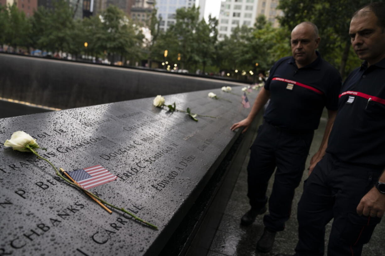 Visitors browse the south pool as flowers and American flags rest among the names of the fallen at the National September 11 Memorial & Museum, Thursday, Sept. 9, 2021, in New York.