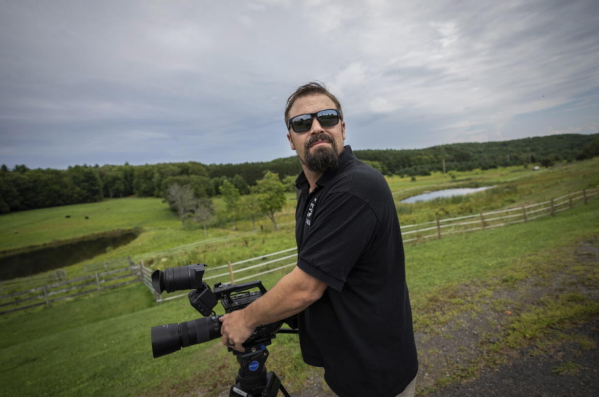 Korey Rowe uses his video camera near his home in Oneonta, N.Y. on Thursday, Aug. 12, 2021. Korey Rowe served tours in Iraq and Afghanistan and returned to the U.S. in 2004 traumatized and disillusioned. His experiences overseas and nagging questions about Sept. 11, 2001 convinced him America's leaders were lying about what happened that day and the wars that followed. (AP Photo/Robert Bumsted) (Ted S.