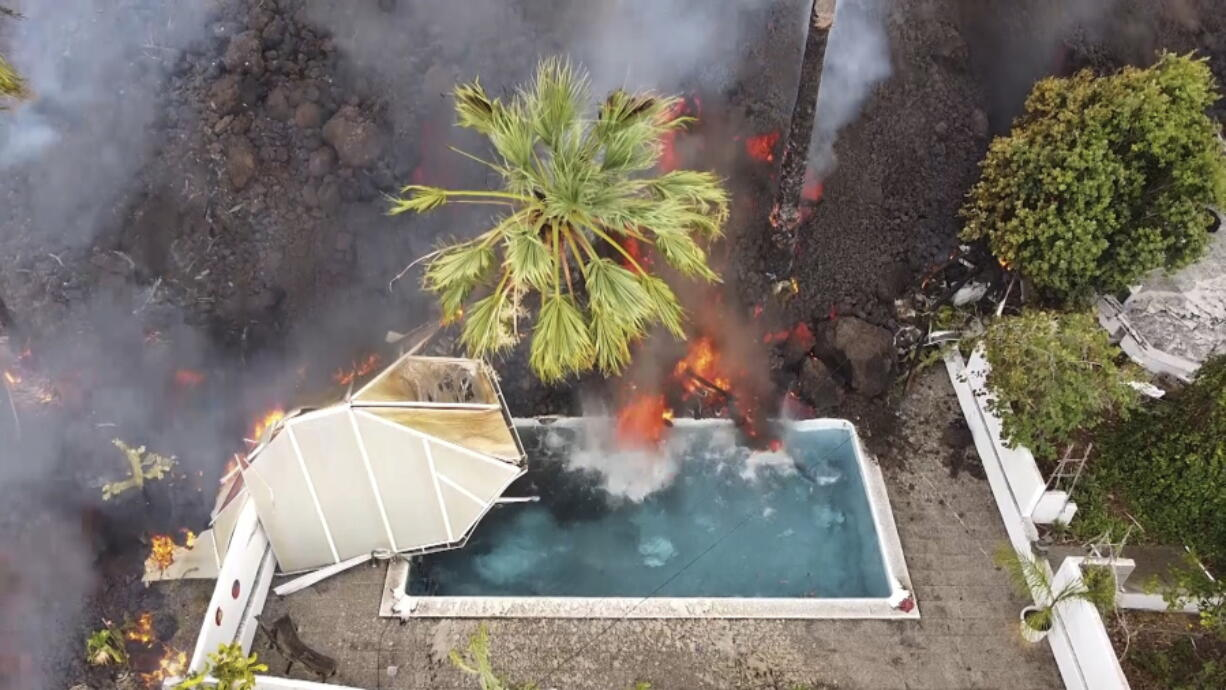 Hot lava reaches a swimming pool after an eruption of a volcano on the island of La Palma in the Canaries, Spain, Monday, Sept. 20, 2021. Giant rivers of lava are tumbling slowly but relentlessly toward the sea after a volcano erupted on a Spanish island off northwest Africa. The lava is destroying everything in its path but prompt evacuations helped avoid casualties after Sunday's eruption.