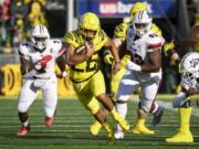 Oregon running back Travis Dye (26) runs past Stony Brook defensive lineman Casey Williams (2) and Stony Brook defensive lineman Dakar Edwards (93) during the first quarter of an NCAA college football game Saturday, Sept. 18, 2021, in Eugene, Ore.