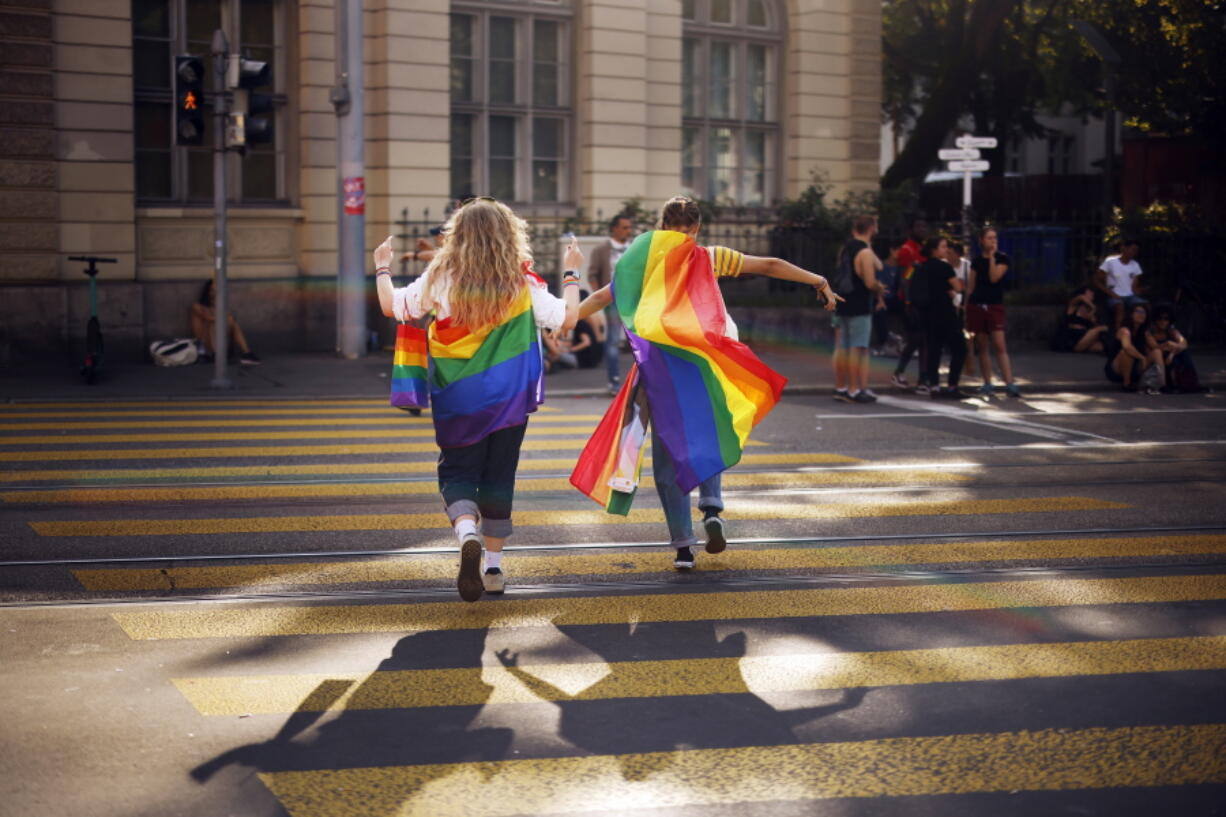"""FILE - In this Saturday, Sept. 4, 2021 file photo, people take part in the Zurich Pride parade in Zurich, Switzerland, with the slogan """"Dare. Marriage for all, now!"""" (Trau Dich. Ehe fuer alle. Jetzt!) for the rights of the LGBTIQ community. Swiss voters will wrap up a referendum on Sunday Sept. 26, 2021, to decide whether to allow same-sex marriage in the rich Alpine country, with supporters hoping for a big step toward ending discrimination against gays and lesbians while opponents fear what they consider an erosion of traditional family values."""