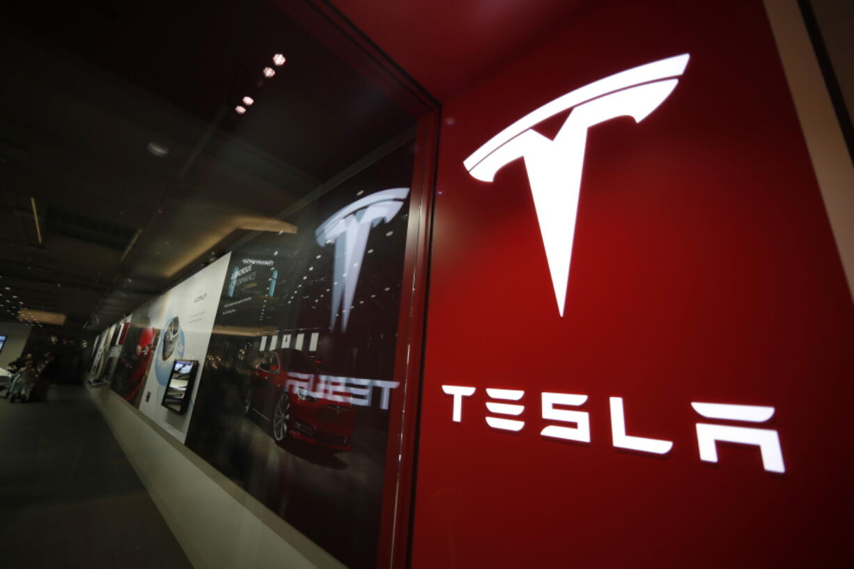FILE - This Feb. 9, 2019, file photo shows a sign bearing the company logo outside a Tesla store in Cherry Creek Mall in Denver. Federal officials said Friday, Sept. 17, 2021 they will investigate a fiery Tesla crash that left two people dead in South Florida. Three investigators with the National Transportation Safety Board are traveling next week to Coral Gables, where a Tesla Model 3 left the roadway and collided with a tree Monday, the agency announced on Twitter.