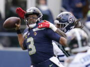 Seattle Seahawks quarterback Russell Wilson is pressured by Tennessee Titans outside linebacker Bud Dupree, right, late in the fourth quarter.