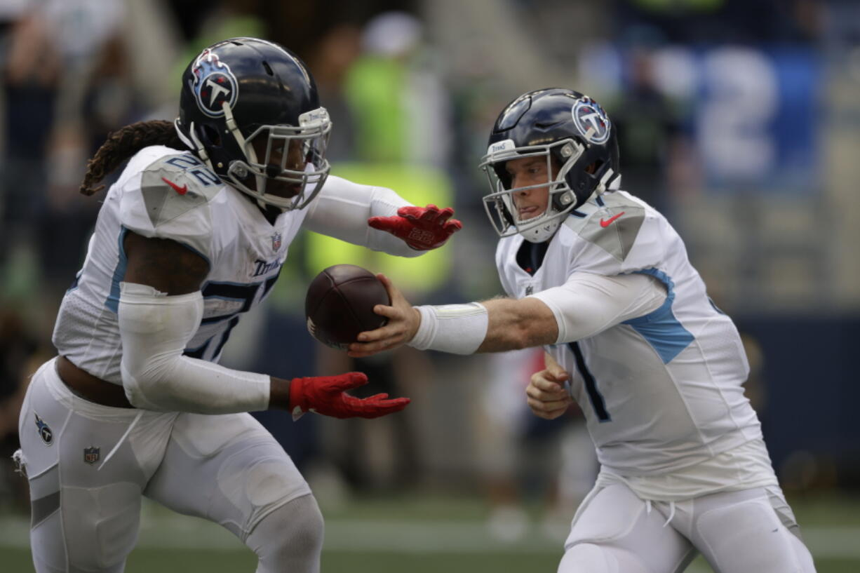 Tennessee Titans quarterback Ryan Tannehill, right, hands off to running back Derrick Henry during the second half of an NFL football game against the Seattle Seahawks, Sunday, Sept. 19, 2021, in Seattle. The Titans won 33-30 in overtime.