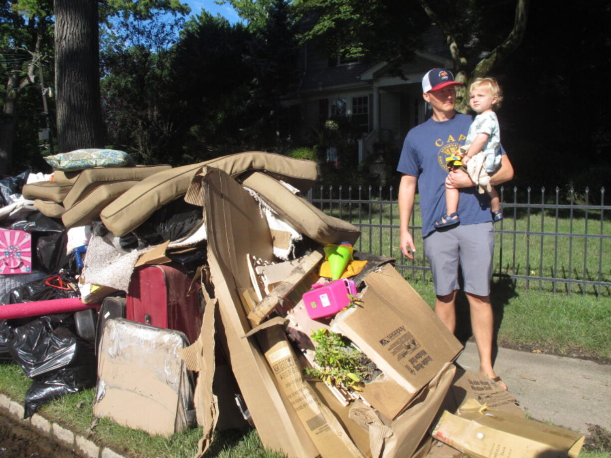 Dave Coughlin carries his 1-year-old son Thomas to their car to get him out of their flood-damaged home in Cranford N.J. on Saturday Sept. 4, 2021. His home, like many others impacted by the remnants of Tropical Storm Ida, has sewage in the basement that needs to be cleaned out.
