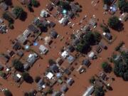 In a satellite image provided by Maxar Technologies, homes along Boessel Ave., in Manville, N.J. are surrounded by floodwaters Thursday, Sept.