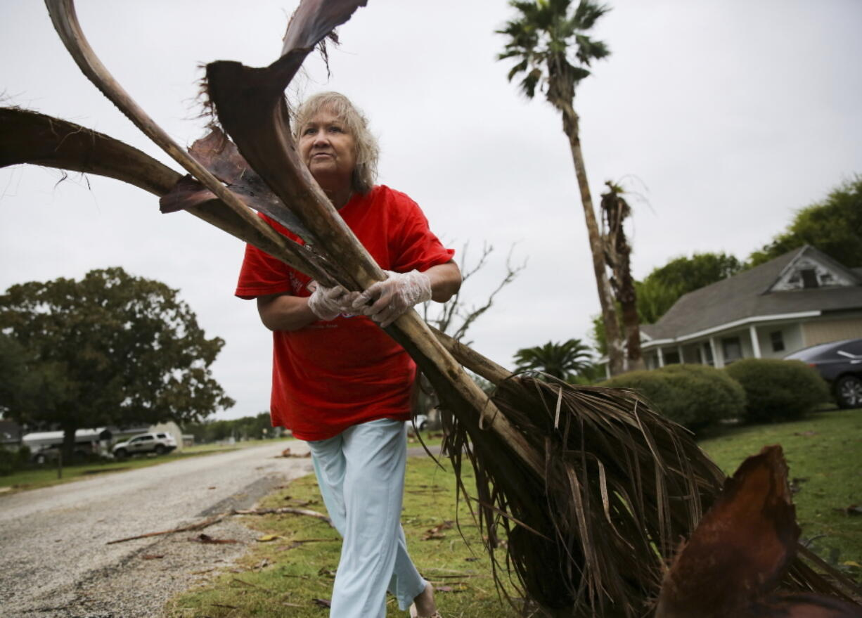 Alfa Alamia cleans up her brother's yard in Palacios, Texas following Hurricane Nicholas on Tuesday, Sept. 14, 2021. Alamia has lived in Palacios since she was 12.