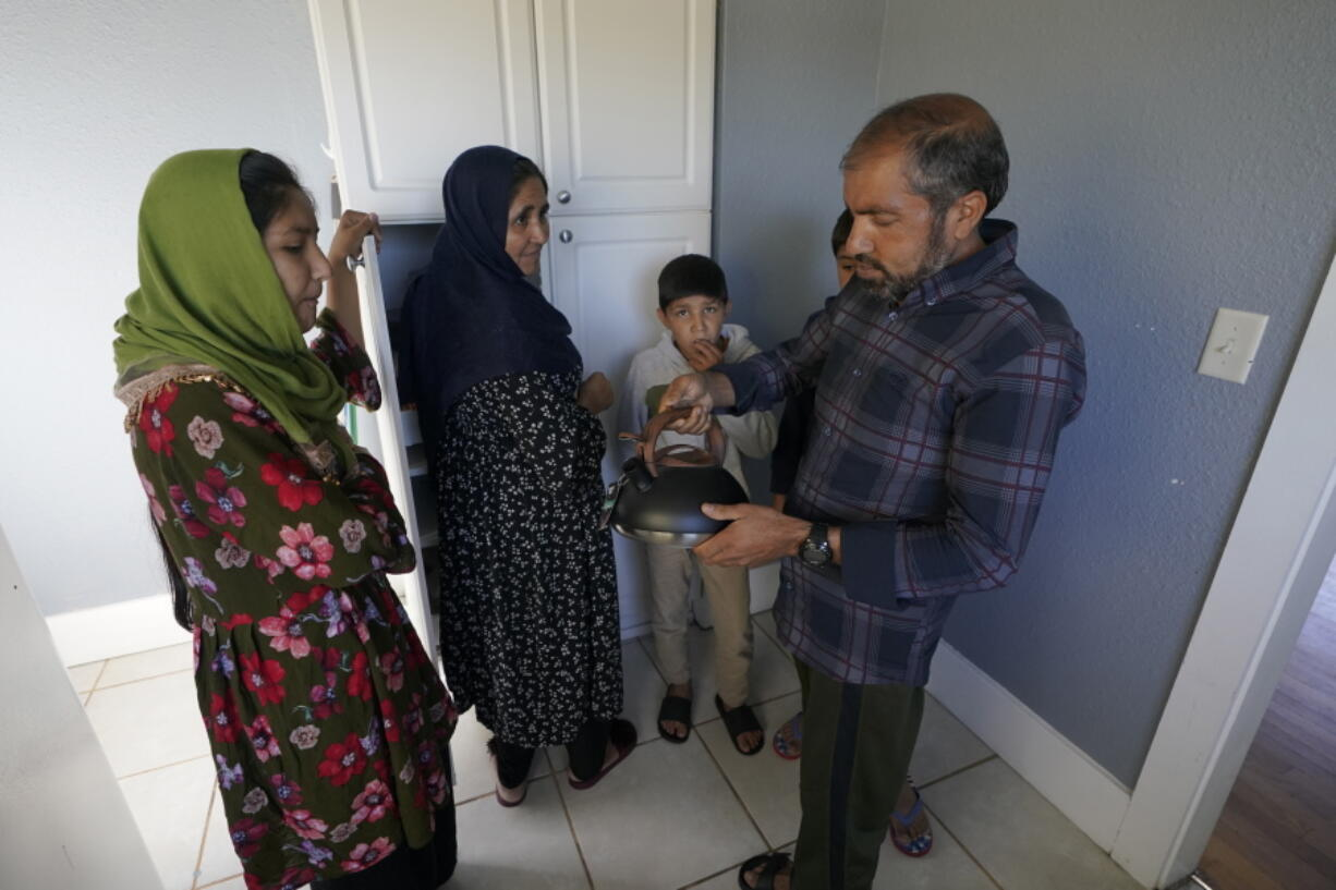 Abdul, right, who worked as a mechanic before he left Kabul, Afghanistan with his family about a month ago, shows his family a donated tea kettle as they stand in the kitchen of a rental house, Thursday, Sept. 16, 2021, that has been provided as a place for them to stay in Seattle. The home is owned by Thuy Do, who was nine years old when her family arrived in the United States from Vietnam in the 1980s. Now Do and her husband have offered their vacant rental home to refugee resettlement groups to house newly arriving Afghans in need of a place to stay. (AP Photo/Ted S.