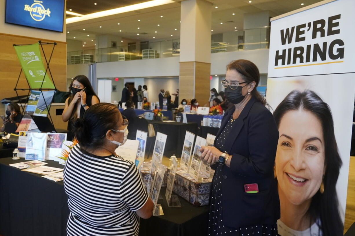 Marriott human resources recruiter Mariela Cuevas, left, talks to Lisbet Oliveros, during a job fair at Hard Rock Stadium, Friday, Sept. 3, 2021, in Miami Gardens, Fla.  The number of Americans seeking unemployment benefits fell sharply last week to 310,000, a pandemic low and a sign that the surge in COVID-19 cases caused by the delta variant has yet to lead to widespread layoffs.