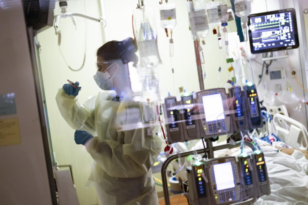 """FILE - In this Tuesday, Aug. 31, 2021 file photo Ann Enderle R.N. attends to a COVID-19 patient in the Medical Intensive care unit (MICU) at St. Luke's Boise Medical Center in Boise, Idaho. Idaho's public health officials say crisis standards of care are """"imminent"""" for the state's most populated region as hospitals in the Boise area continue to be overrun with unvaccinated coronavirus patients. Hospitals in the northern half of the state were given permission to begin rationing care last week."""