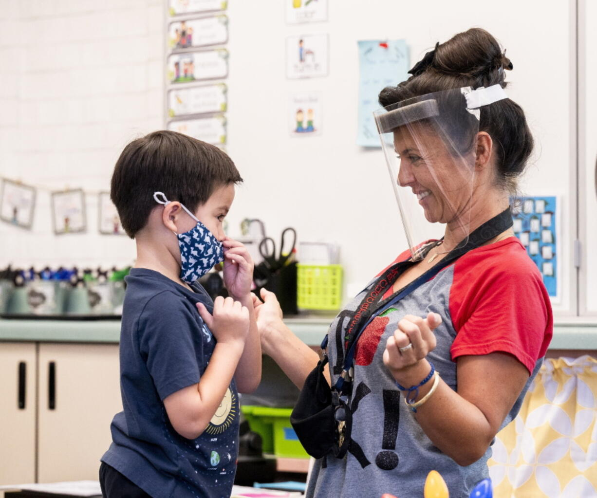 A student gets help with his mask from transitional kindergarten teacher Annette Cuccarese on Aug. 12, the first day of classes at Tustin Ranch Elementary School in Tustin, Calif. Now that California schools have welcomed students back to in-person learning, they face a new challenge: A shortage of teachers and all other staff.