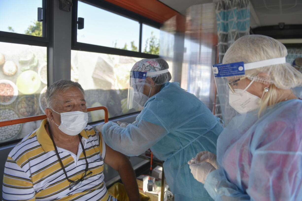 FILE - In this Sept. 4, 2021, file photo, a man receives the Johnson & Johnson vaccine in a bus that serves as a mobile COVID-19 vaccination unit in Bucharest, Romania. In both the U.S. and the EU, officials are struggling with the same question: how to boost vaccination rates to the max and end a pandemic that has repeatedly thwarted efforts to control it. In the European Union, officials in many places are requiring people to show proof of vaccination, a negative test or recent recovery from COVID-19 to participate in everyday activities -- even sometimes to go to work.