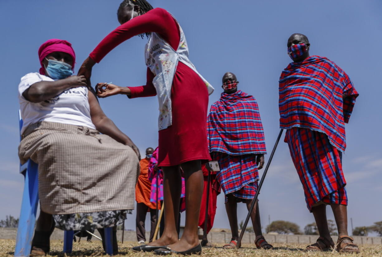 Maasai men queuing to receive the AstraZeneca coronavirus vaccine look over as a woman, who is not, Maasai receives a jab at a clinic in Kimana, southern Kenya Saturday, Aug. 28, 2021. Plans for COVID-19 booster shots in some Western countries are highlighting vast disparities in access to vaccines around the world.