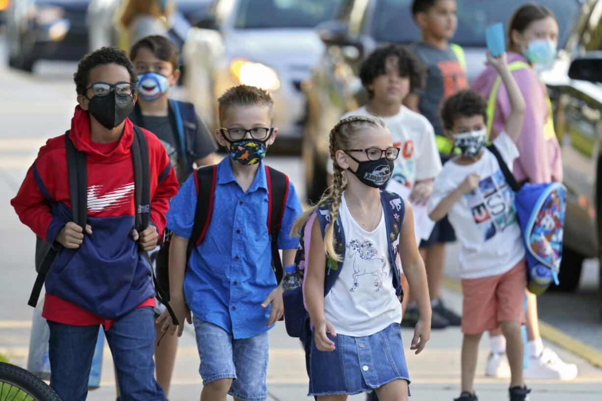 Students wearing protective masks arrive for the first day of school at Sessums Elementary School in Riverview, Fla., on Aug. 10.