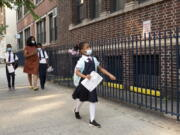A girl leads her mother and brothers as they arrive at Brooklyn's PS 245, Monday, Sept. 13, 2021, in New York. Classroom doors are swinging open for about a million New York City public school students in the nation's largest experiment of in-person learning during the coronavirus pandemic.