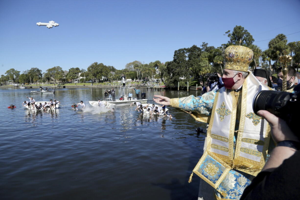 """FILE - In this Wednesday, Jan. 6, 2021 file photo, His Eminence Archbishop Elpidophoros, Primate of the Greek Orthodox Archdiocese of America throws a cross into Spring Bayou during the 115th year of the annual Epiphany celebration in Tarpon Springs, Fla. Leaders of the Greek Orthodox Archdiocese of America said Thursday, Sept. 16, 2021, that while some people may have medical conditions for not receiving the vaccine, """"there is no exemption in the Orthodox Church for Her faithful from any vaccination for religious reasons."""" Greek Orthodox Archbishop Elpidophoros added: """"No clergy are to issue such religious exemption letters,"""" and any such letter """"is not valid."""" (Douglas R."""